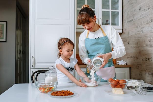 여자는 어머니가 부엌에서 케이크를 준비하는 데 도움이