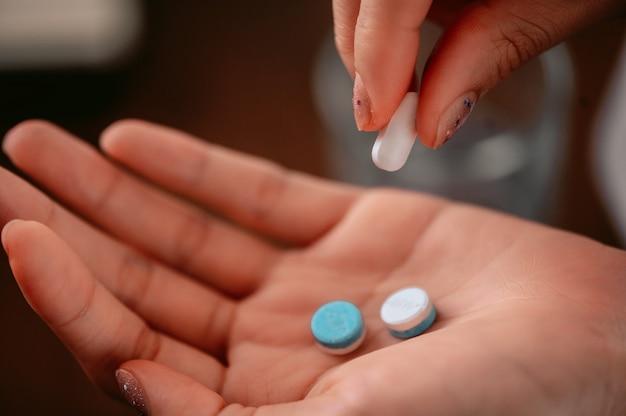 女性は白と青の錠剤を手に持っています。ヘルスケアと医学の概念、丸薬をクローズアップ。