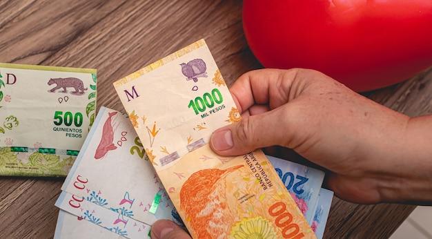 アルゼンチンのお金の紙幣を持っている女性