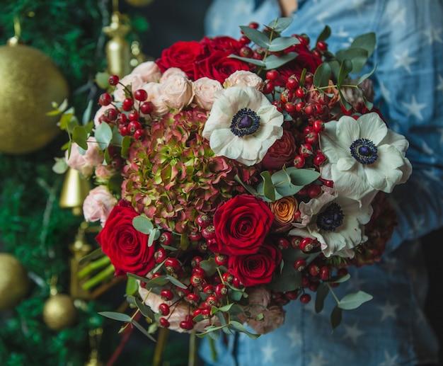 クリスマス装飾壁backgorundの手で秋の色の花の花束を保持している女性。