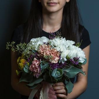 部屋の壁backgorundの手にカラフルな、ほとんど白い牡丹の花束を保持している女性。