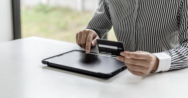 Женщина, держащая кредитную карту и касаясь планшета, заполняет данные своей кредитной карты, чтобы оплатить заказ на сайте онлайн-покупок. интернет-магазины и концепция оплаты кредитной картой.