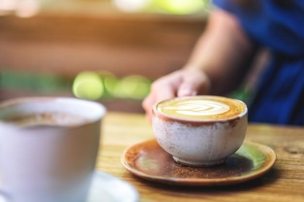 아침에 나무 탁자에 뜨거운 라떼 커피 한 잔을 들고 있는 여성