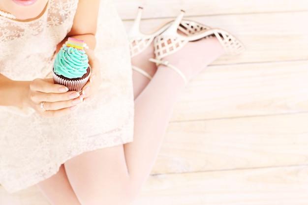 木製の背景の上においしいカップケーキを保持している女性
