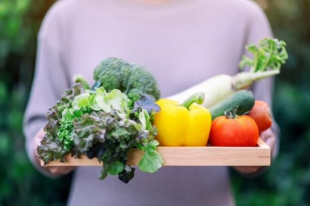 Женщина, держащая свежую овощную смесь в деревянном подносе