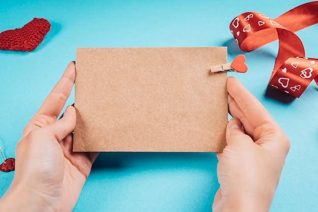 バレンタインデーのために彼女の手にハートとクラフト紙の手紙を持っている女性