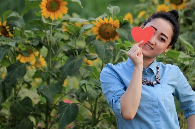 Женщина держит символ любви с веселым выражением лица