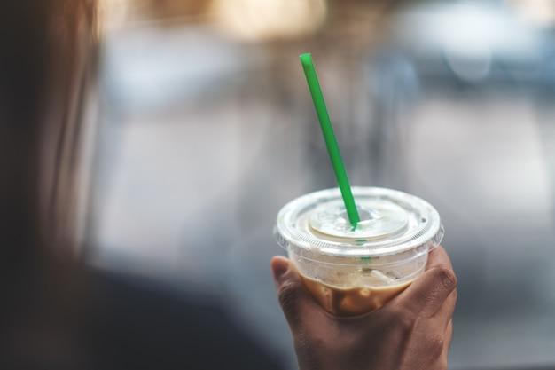 ストローでアイスコーヒーのプラスチックガラスを保持している女性