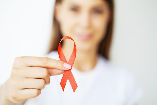 赤いリボンを抱える女性がエイズを克服した後の危機的状況から浮上