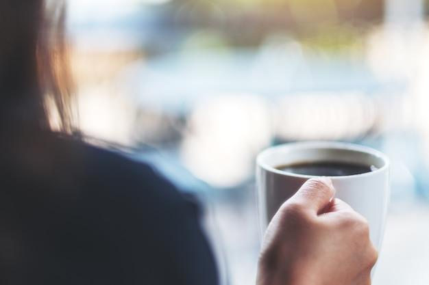 Женщина держит чашку белого горячего кофе с размытым фоном