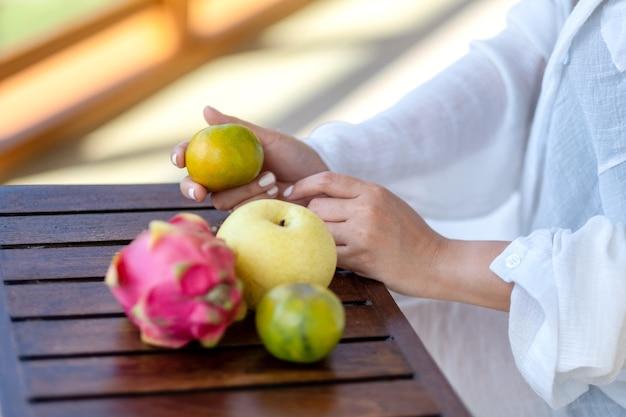小さな木製のテーブルに梨とドラゴンフルーツとオレンジを保持している女性