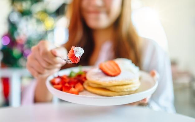 いちごとホイップクリームとフォークでパンケーキを持って食べる女性