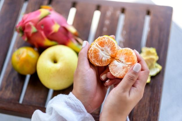 小さな木製のテーブルの上で梨とドラゴンフルーツと一緒に食べるためにオレンジを持って皮をむく女性