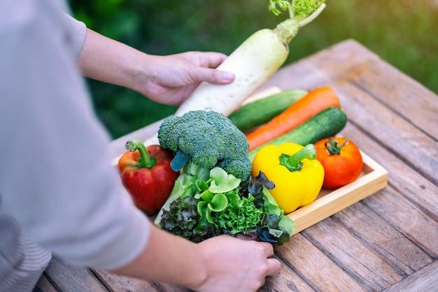 Женщина, держащая и собирающая свежую овощную смесь с деревянного подноса на столе