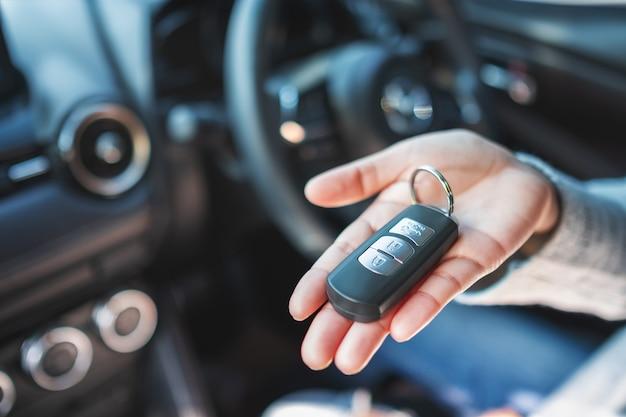 Женщина держит и показывает ключ от машины, сидя в машине
