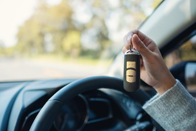 차에 앉아 차 키를 들고 보여주는 여성