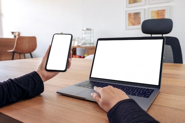 빈 흰색 화면과 사무실에서 나무 테이블에 노트북 모형 휴대 전화를 들고 사용하는 여자