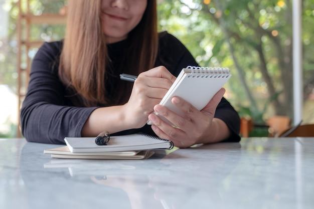 ノートを押しながら書く女性