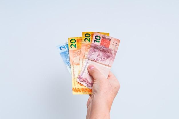 흰색 배경에 고립 된 브라질 실제 지폐를 들고 여자