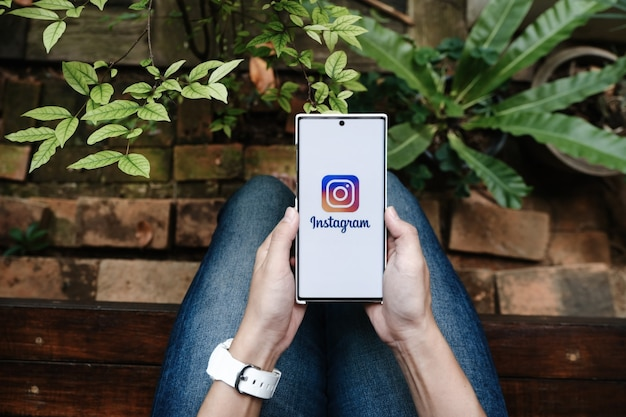 Chiangmai, thailand - 2021년 7월 9일: 화면에 instagram 애플리케이션이 있는 스마트폰을 들고 있는 여성. instagram은 스마트폰용 사진 공유 앱입니다.