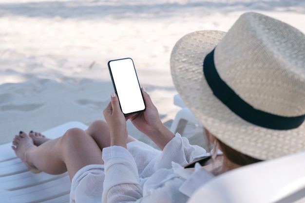 Женщина держит белый мобильный телефон с пустым экраном рабочего стола, лежа на шезлонге на пляже