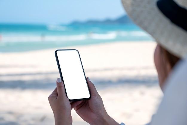 Женщина держит белый мобильный телефон с пустым экраном рабочего стола на фоне голубого неба на пляже