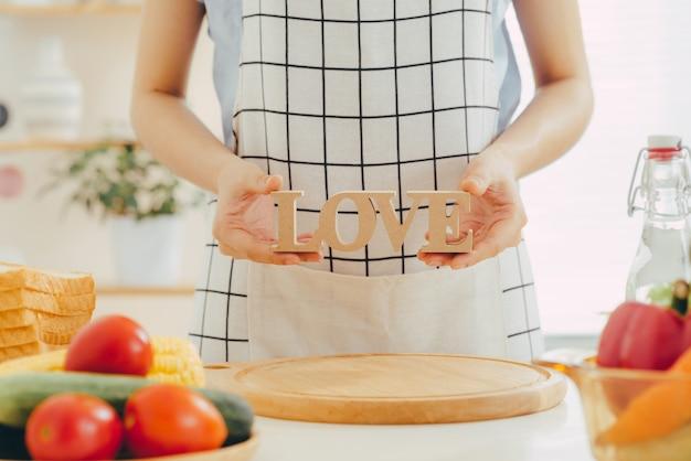キッチンで料理をしながら木製の文字loveを保持している女性。