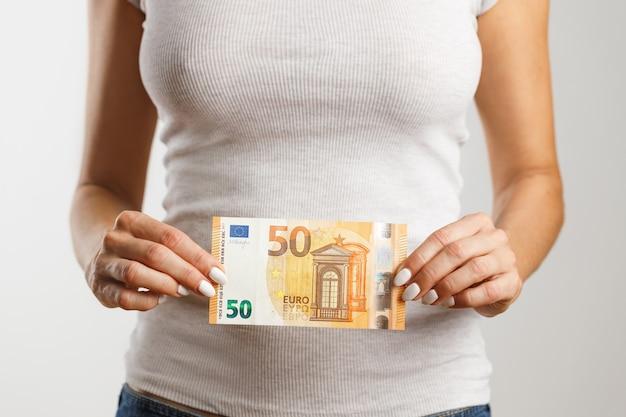 女性は50ユーロを手に持っています。金融および商業の概念。