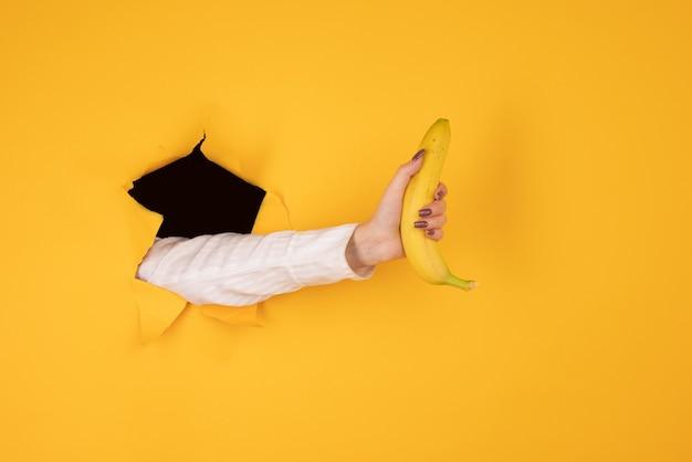 引き裂かれた黄色い紙の穴から挿入されたバナナを手に持った女性