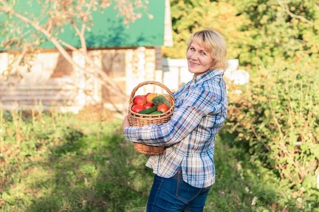 Женщина держит корзину с овощами в саду. женщина средних лет на заднем дворе собирает вкусные и полезные фрукты.