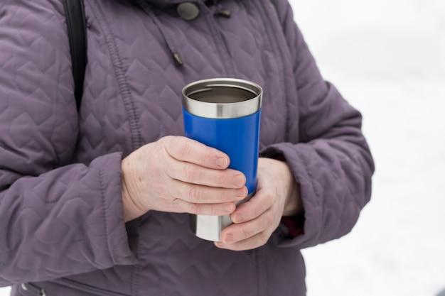 여자는 그녀의 손에 뜨거운 차와 함께 파란색 thermocup을 보유하고 있습니다.