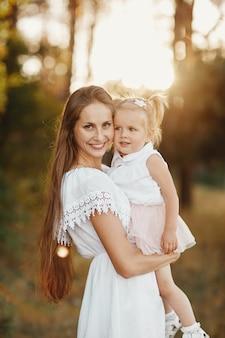 Женщина держит на руках ребенка в парке.