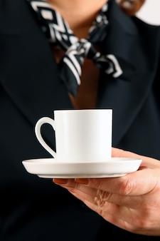 女性はブラックコーヒーやお茶で満たされたカップを持っています