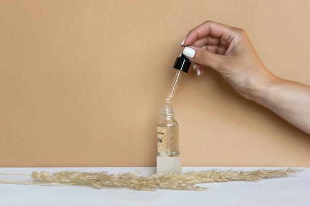 女性は、血清または天然エッセンシャルオイルでボトルのスポイトを保持します