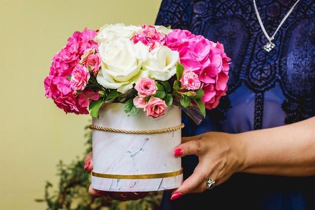 女性が手に花束を持っています
