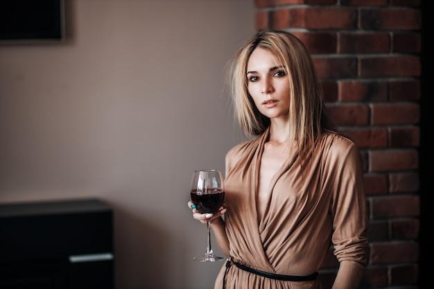 女性がレストランで赤ワインのグラスを持っています