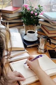 한 여성이 펜을 들고 책으로 둘러싸인 사무실 책상 위의 공책에 메모를 하고 있다