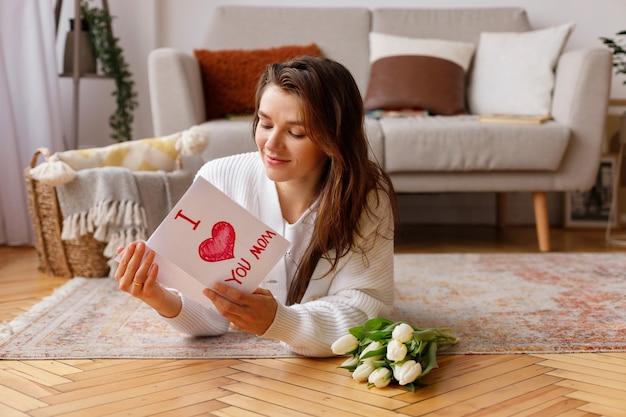한 여성이 3 월 8 일까지 엽서를 들고 거실 바닥에 튤립 꽃다발 옆에 누워 있습니다.