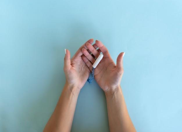 한 여성이 손에 위생 탐폰을 들고 있습니다. 위생 및 바디 케어 개념
