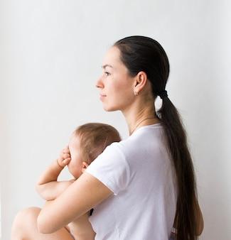 Женщина держит маленького ребенка, матери и ребенка на белом фоне крупным планом. день защиты детей, день матери