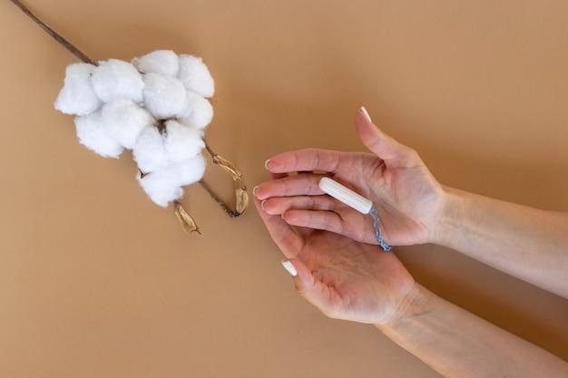한 여성이 손에 흰색 위생 탐폰을 들고 있습니다. 월경일. 위생 및 바디 케어 개념