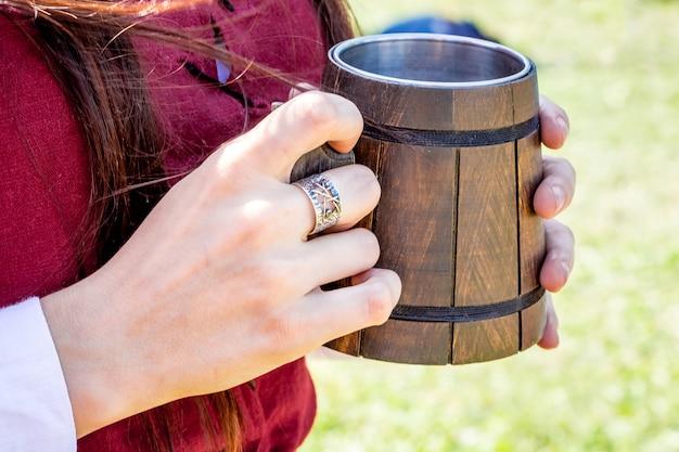 여자는 그녀의 hands_에 시원한 음료와 함께 나무 찻잔을 보유