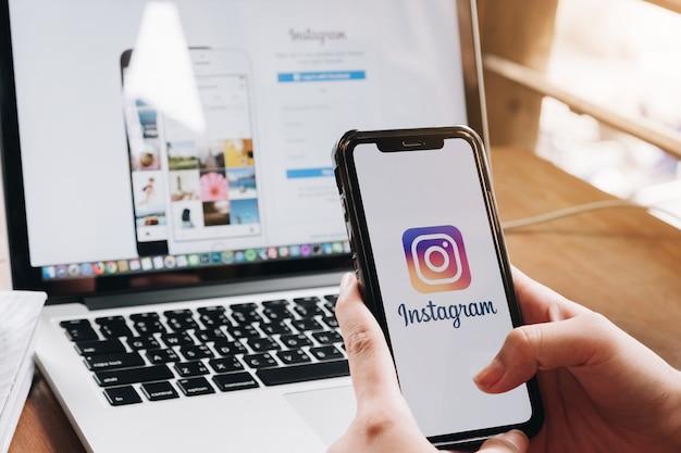 女性がカフェの画面でinstagramアプリケーションを使用してスマートフォンを保持しています。