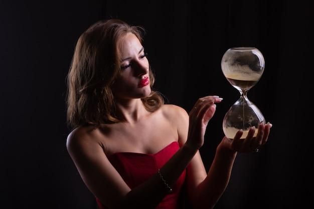 女性は彼女の手で大きな砂の時計を持っています