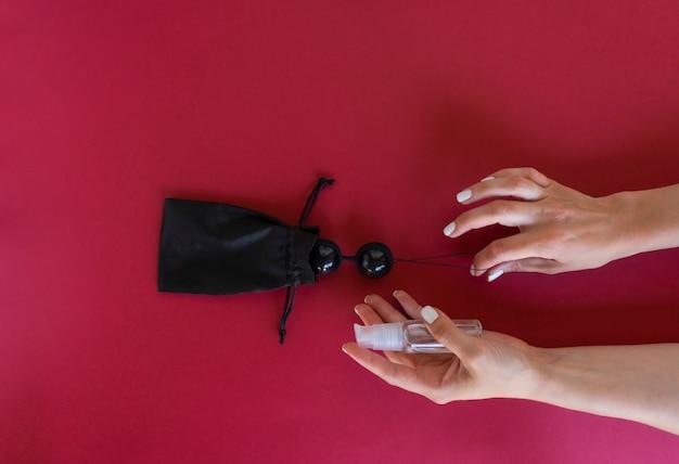 한 여성이 근육 운동을 할 준비가 된 검은 질 공을 들고 있습니다. 강한 질 근육
