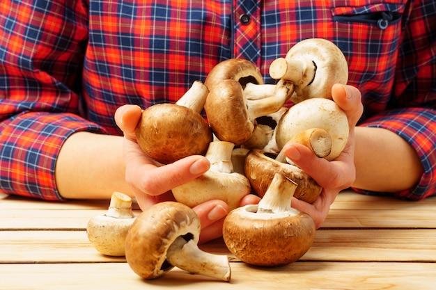 여자는 그녀의 손에 샴 피뇽 버섯을 보유하고 있습니다. 적절한 영양과 건강의 개념
