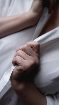 한 여성이 남성용 흰색 셔츠를 위해 손을 잡고 있습니다. 얼굴 없는 사진