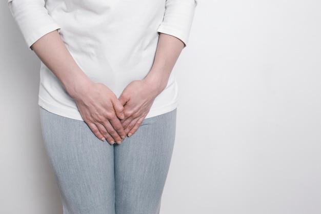 여자는 아픈 가랑이를 위해 손을 잡고 있습니다. 하복부의 부인과 문제. 방광의 염증.