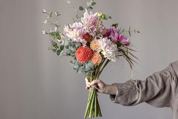 Женщина держит в руке праздничную цветочную композицию с яркими цветами хризантемы, праздничный букет.