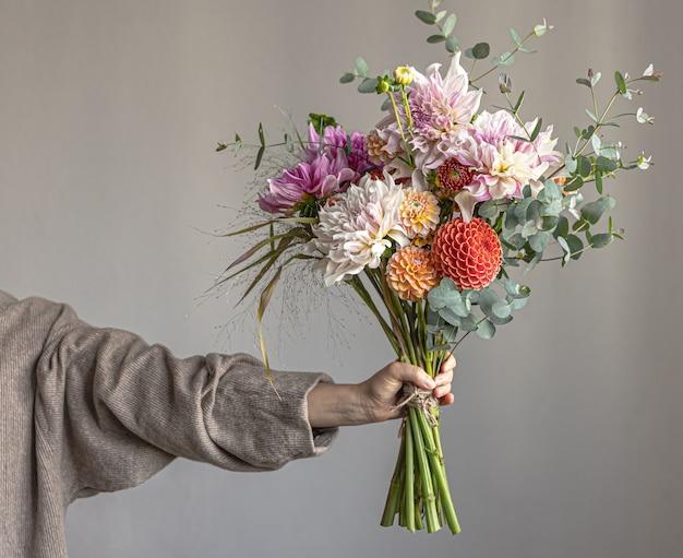 한 여성이 밝은 국화 꽃과 축제 꽃다발을 손에 들고 있습니다.